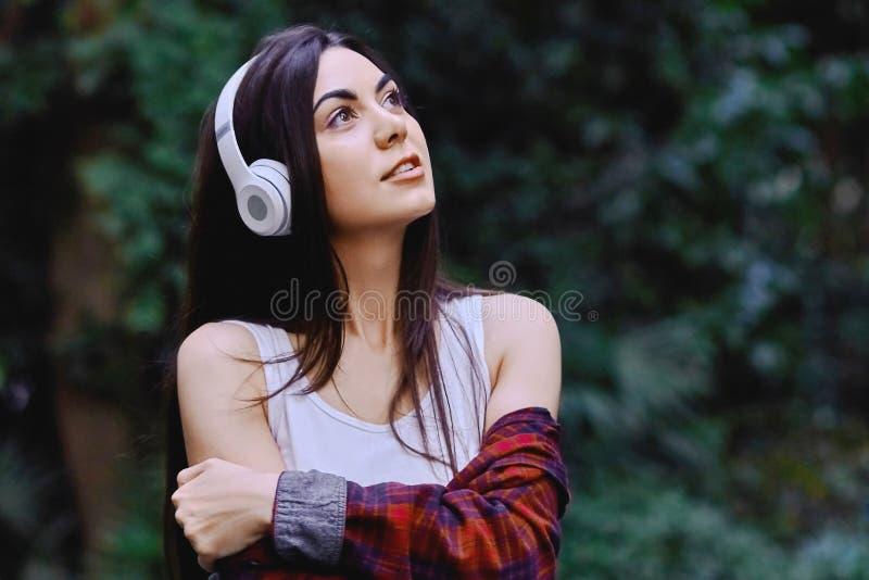 听到音乐的年轻微笑的妇女,通过在她的头的耳机 免版税库存图片