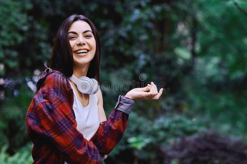 听到音乐的年轻微笑的妇女,通过在她的头的耳机 免版税库存照片