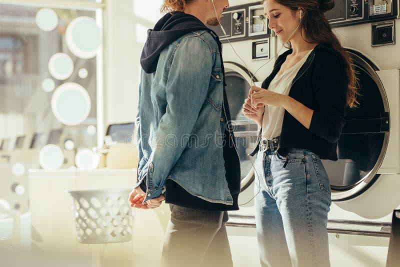 听到音乐的微笑的夫妇站立在洗衣房 免版税图库摄影