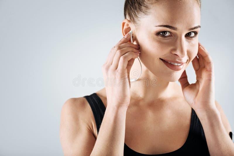 听到音乐的微笑的妇女在训练以后 库存图片