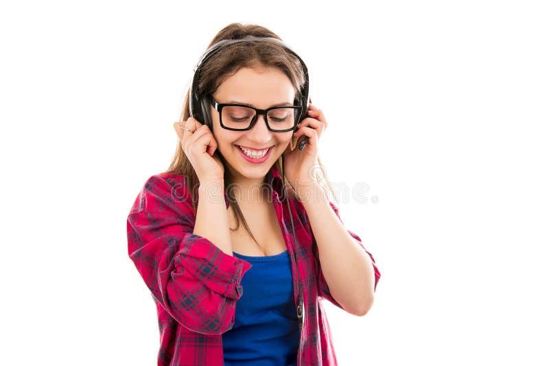 听到音乐的微笑的少年妇女 免版税库存照片