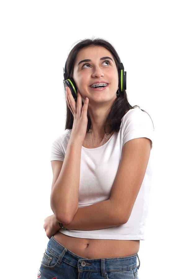 听到音乐的愉快的少年女孩隔绝在白色b 库存图片