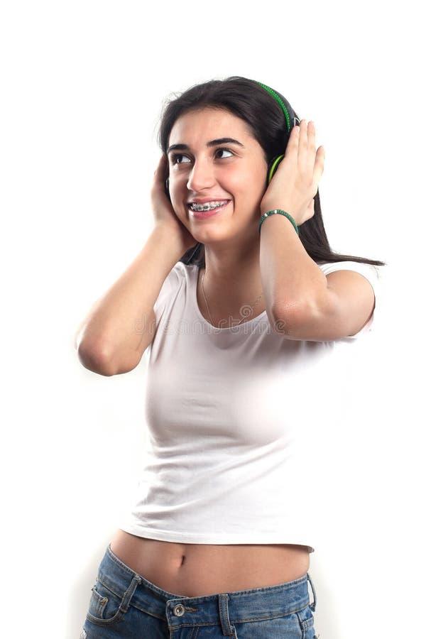 听到音乐的愉快的少年女孩隔绝在白色b 免版税库存图片