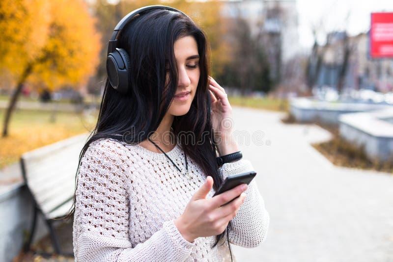 听到音乐的愉快的青少年的妇女和在秋天公园放松 黄色树,美好的下降时间 免版税库存图片