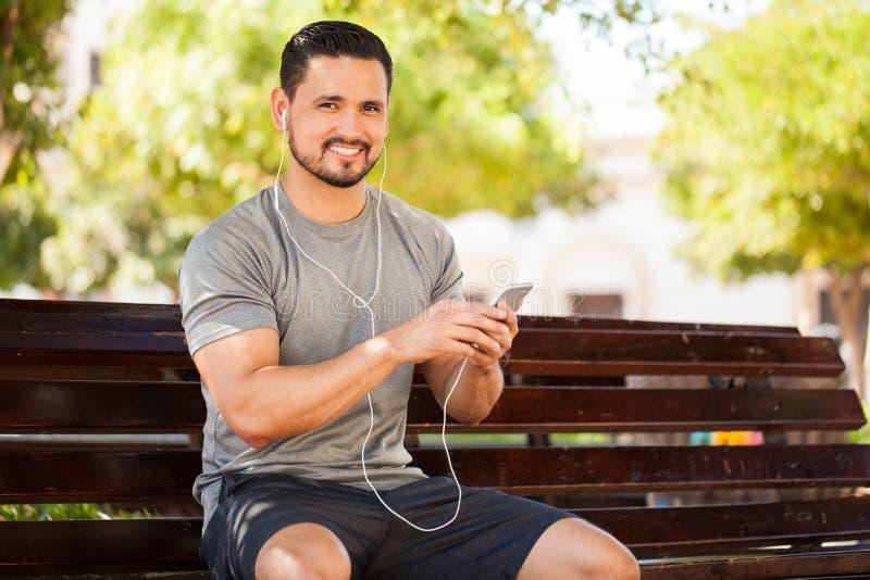 听到音乐的拉丁年轻人在公园 库存图片