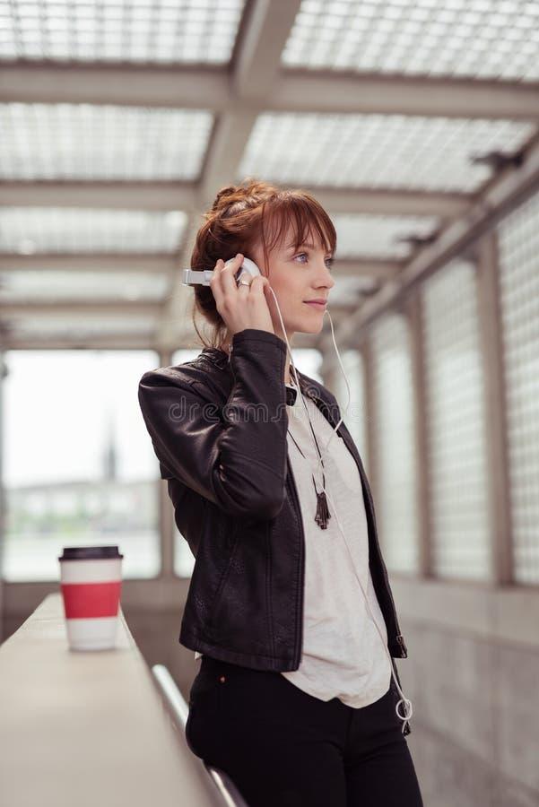 听到音乐的时髦的妇女在栏杆 免版税图库摄影