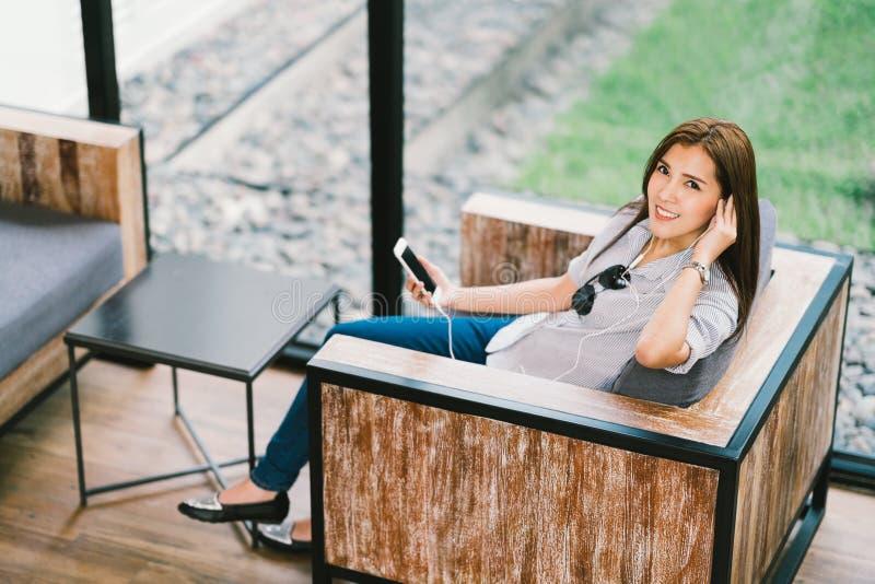 听到音乐的美丽的亚裔妇女使用智能手机,坐在咖啡馆或咖啡店 松弛爱好活动概念 免版税库存照片