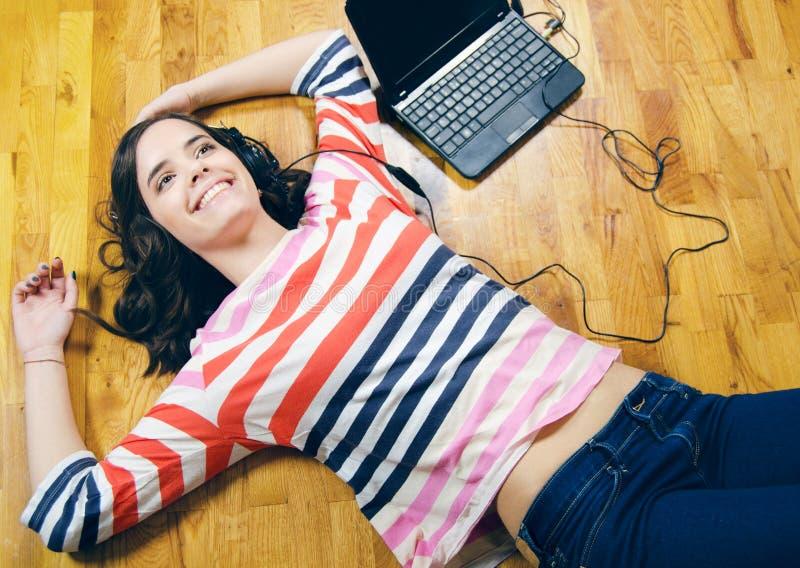 听到音乐的美丽的十几岁的女孩,当说谎在地板上时 库存图片
