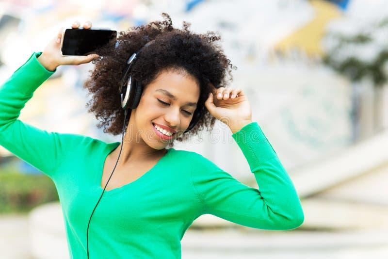 听到音乐的美国黑人的妇女 免版税库存照片