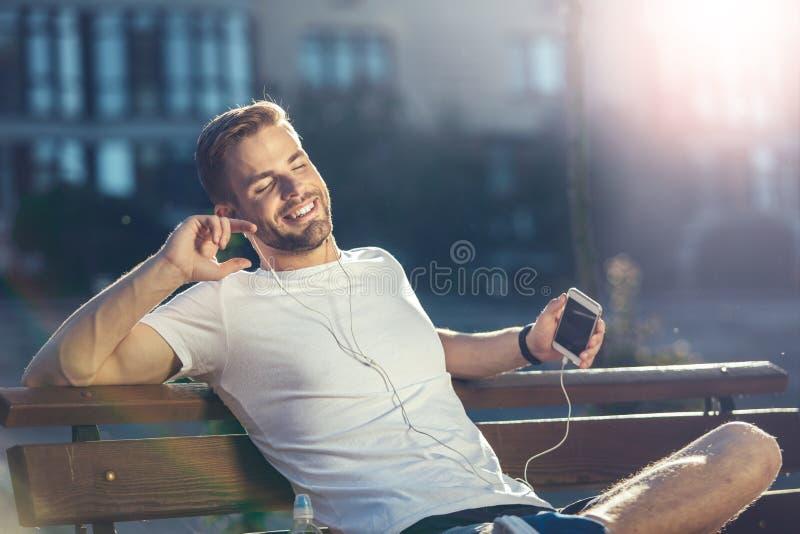 听到音乐的轻松的人外面 免版税库存照片