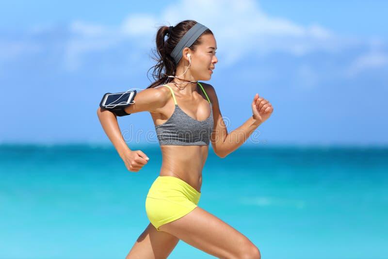 听到音乐的运动员连续妇女赛跑者 库存照片