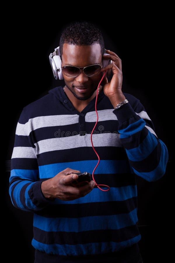听到音乐的非裔美国人的人隔绝在黑backgr 图库摄影