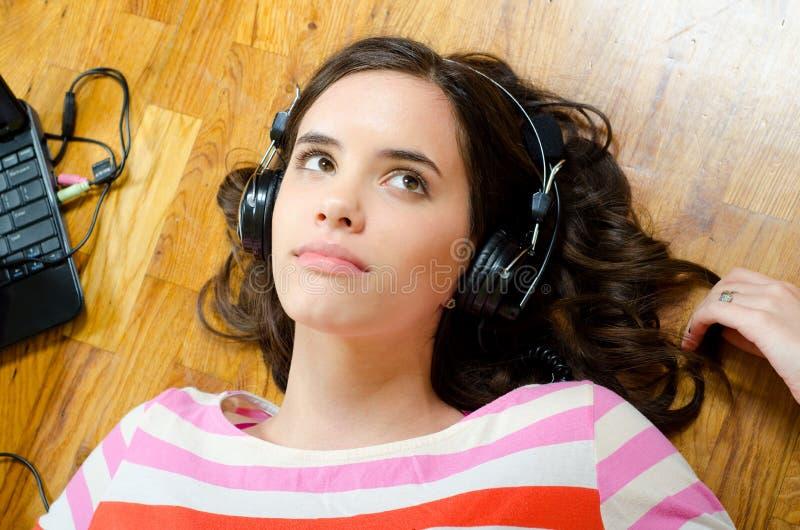 听到从笔记本的音乐的美丽的十几岁的女孩 库存照片