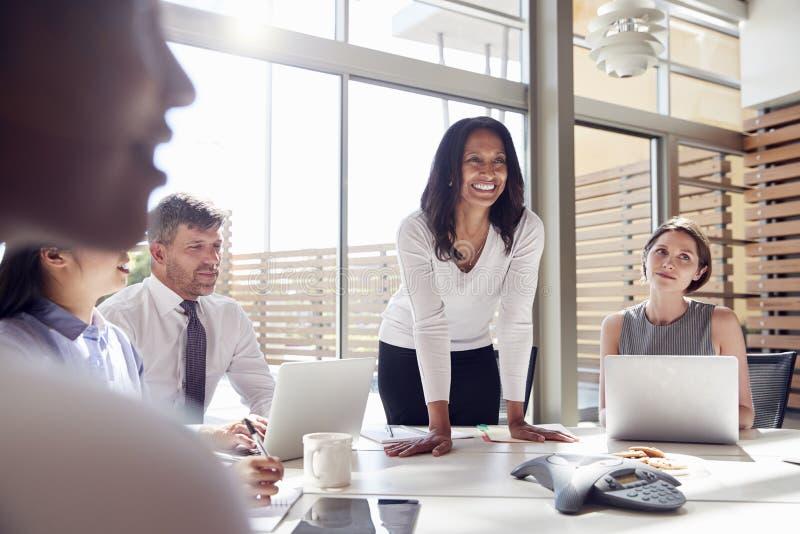 听同事的微笑的女性经理在会议上 库存照片