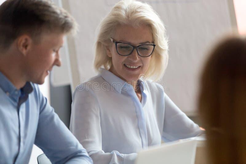 听同事的成熟女实业家在公司会议上 免版税库存照片