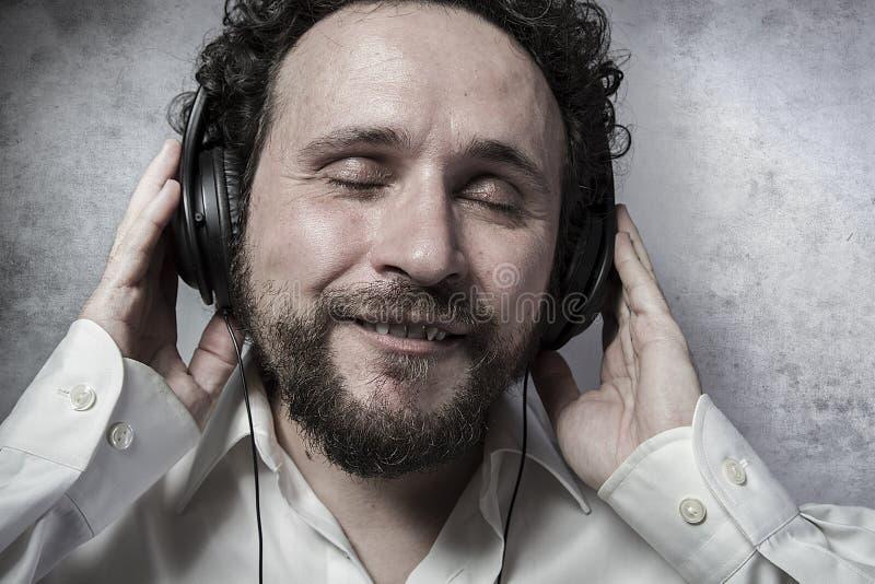 听和享受与耳机的音乐,白色衬衣的人 库存照片