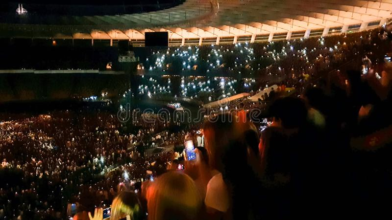 听和观看在音乐节的人Defocused照片大摇滚乐音乐会在大体育场 爱好者人群  库存图片