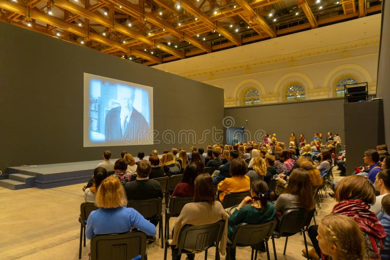 听和观看屏幕的历史会议的人们 r r 免版税库存照片