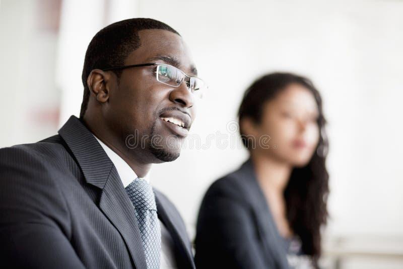 听在业务会议上的微笑的商人 库存图片