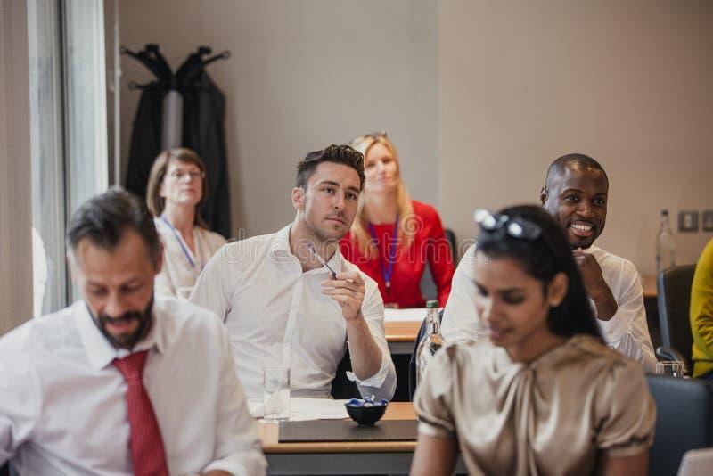 听在会议期间的商人 免版税库存照片