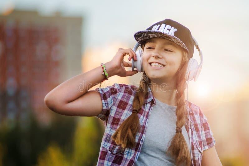 听在耳机的音乐,都市街道样式,黑盖帽的室外街道样式行家dj妇女的女孩和 库存图片