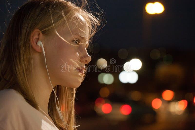 听在街道背景的音乐画象的十几岁的女孩 青少年女孩的耳机 免版税图库摄影
