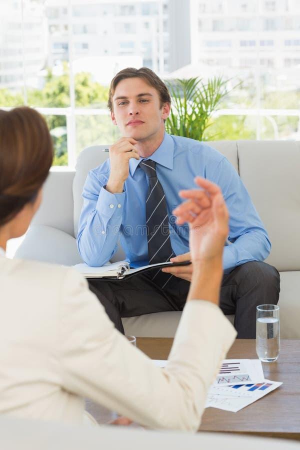 听女性同事的年轻商人坐长沙发 库存照片