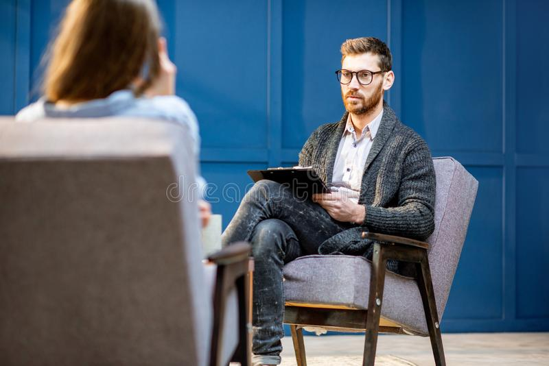 听妇女客户的心理学家在办公室 免版税库存图片