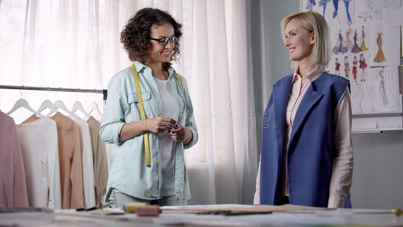 听客户的工作室所有者祝愿新的外套的装饰,适合 库存图片