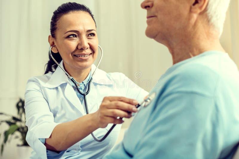 听心脏拍打的放光的女性医生 免版税库存图片