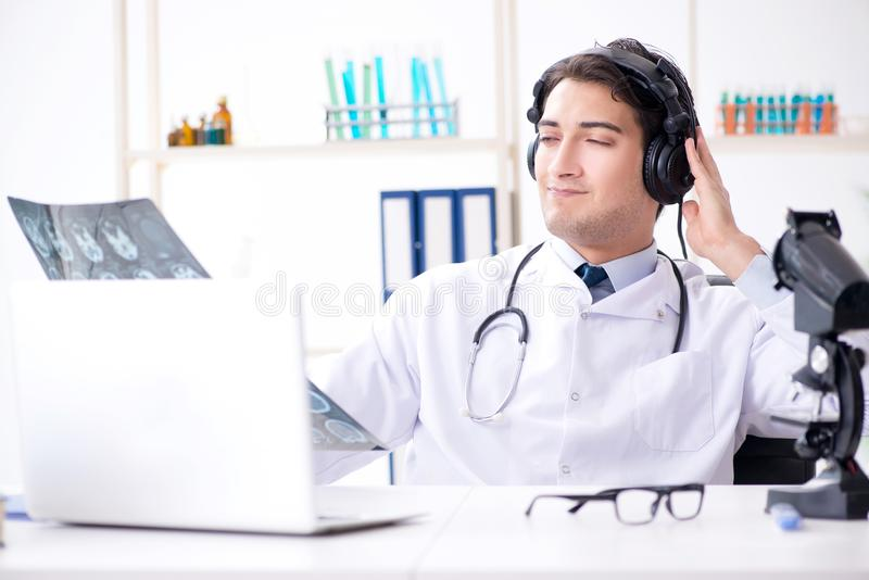 听患者的男性医生在远程医学会议期间 免版税库存照片