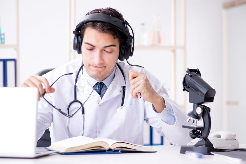 听患者的男性医生在远程医学会议期间 库存图片