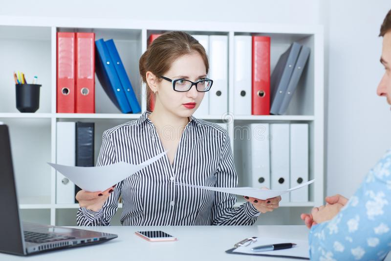 听情感母上司的男性经理拿着文件,指向纸 争执或论据关于 免版税图库摄影