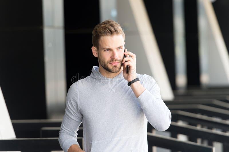 听我 人胡子走与智能手机,都市背景 有胡子严肃的面孔谈话智能手机的人 人 免版税库存照片