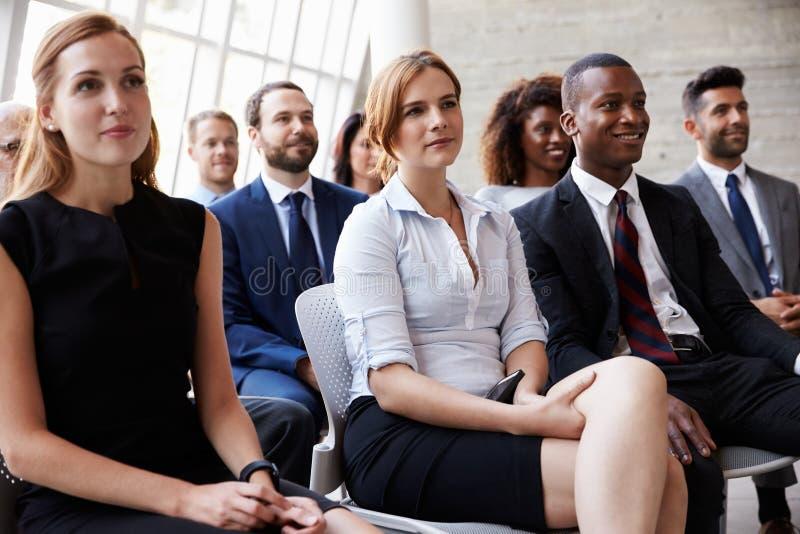 听报告人的观众在业务会议 免版税图库摄影
