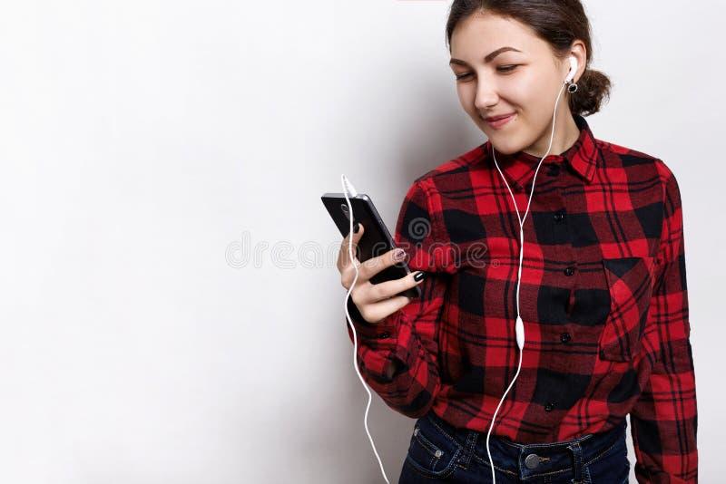 听殷勤地audiobook的微笑的学生女孩画象,当准备对检查在大学时 che的女性少年 免版税库存照片
