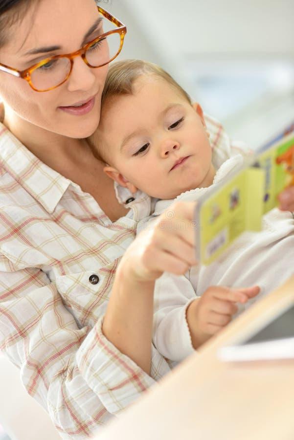 听母亲的故事的婴孩的愉快的片刻 免版税库存图片