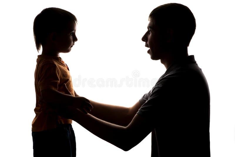 听父母的指示父亲和littleson的剪影  免版税库存照片