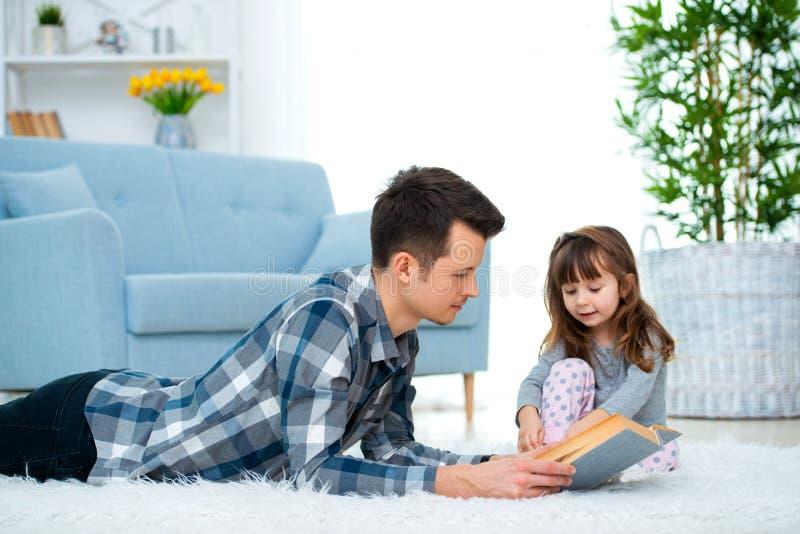听爸爸读书童话当中的逗人喜爱的女孩一起说谎在温暖的地板上,关心父亲藏品书,家庭爱好 免版税库存照片
