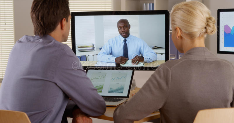 听电视电话会议的经理的雇员 免版税库存图片