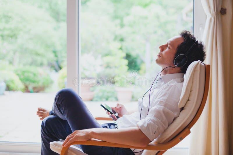 听的松弛音乐在家,坐在轻便折叠躺椅的耳机的轻松的人 库存图片