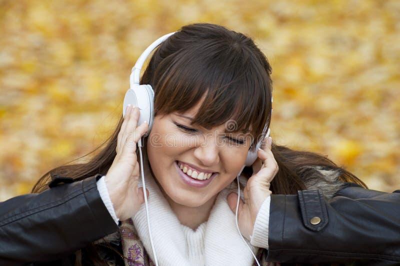 听的音乐纵向妇女 免版税库存图片