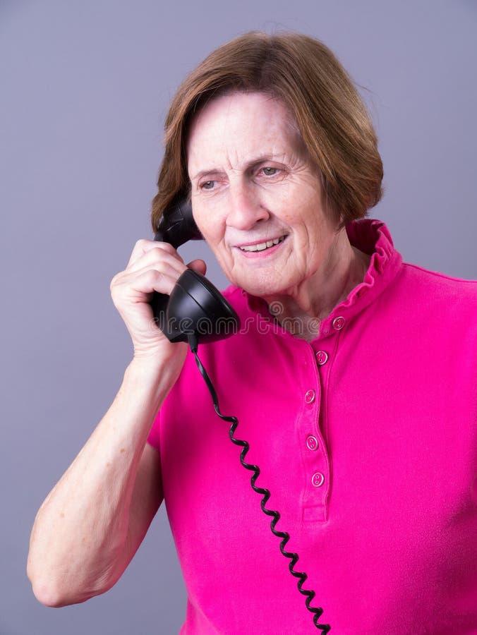 听的高级电话妇女 免版税库存照片