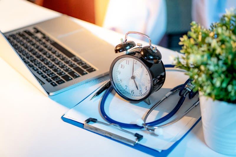 听诊器、剪贴板、时钟和膝上型计算机在医生书桌上 免版税库存图片