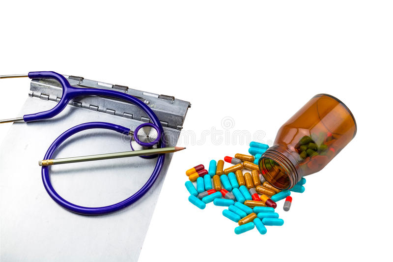 听诊器、病史文件夹剪贴板和五颜六色的片剂医学在黑瓶在白色 免版税库存图片
