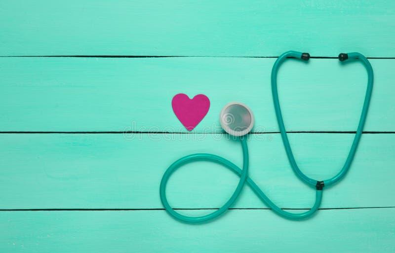 听诊器和心脏在一张蓝色木桌上 诊断的心血管病心脏病学设备 顶视图 库存照片