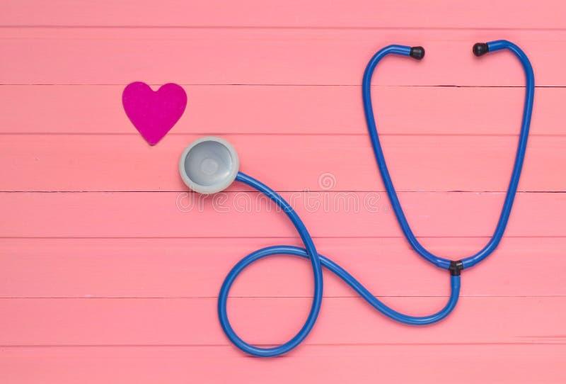 听诊器和心脏在粉红彩笔木桌上 诊断的心血管病心脏病学设备 顶视图 免版税图库摄影