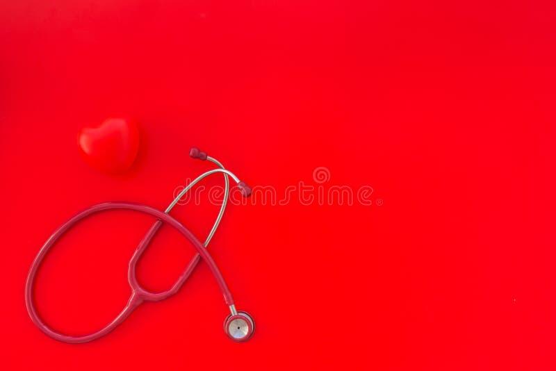 听诊器和心脏心脏疾患诊断和治疗的在红色背景顶视图大模型 免版税库存照片