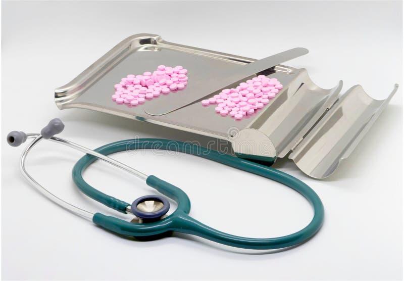 听诊器和桃红色药片在盘子有玻璃的在被隔绝的丝毫 免版税库存照片