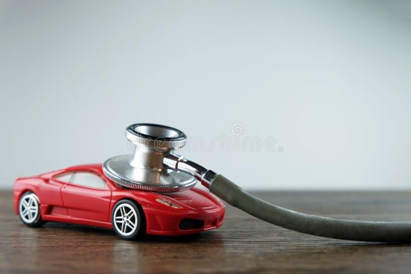 听诊器和汽车在木桌上,汽车核对的概念 免版税库存图片